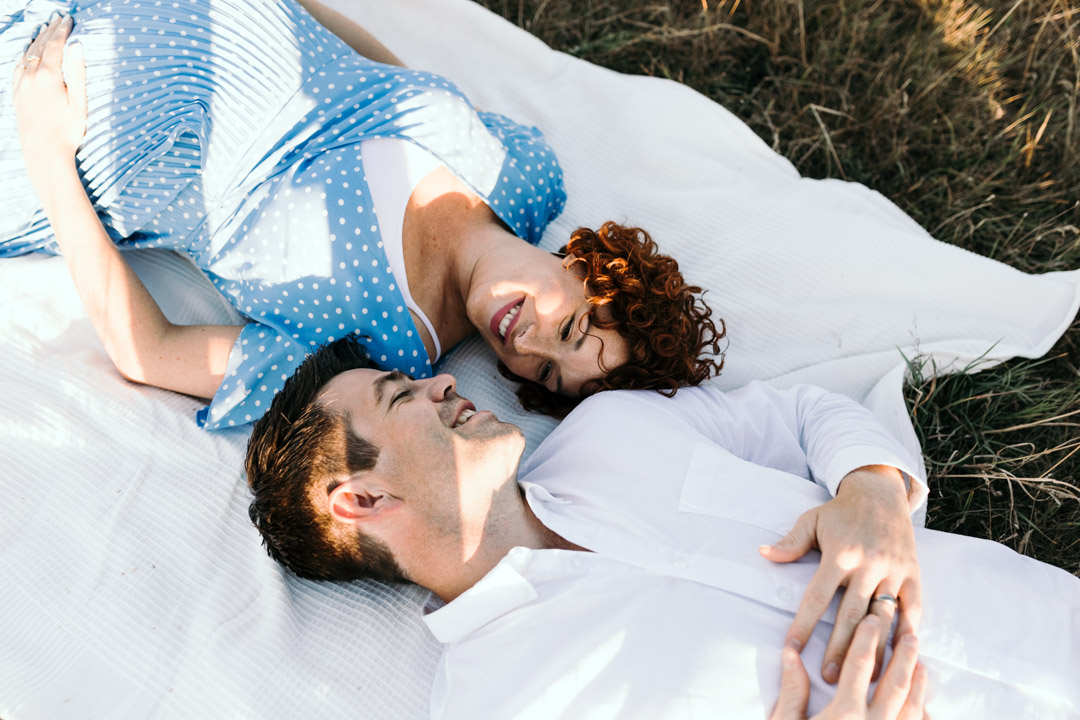 Expecting mum and dad are laying on the blanket and looking at each other. Why I love taking maternity photo sessions. Golden hour maternity photo session. Ewa Jones Photography