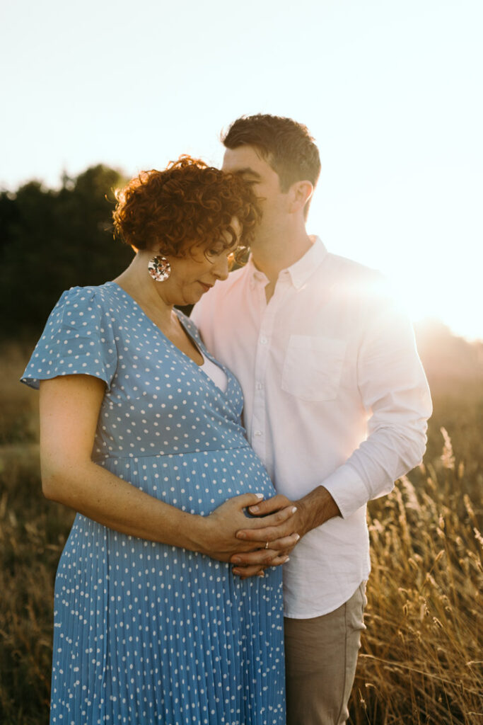 Expecting mum is holding her bump and husband is kissing mum on her head. Golden hour maternity photography in Hampshire. Ewa Jones Photography