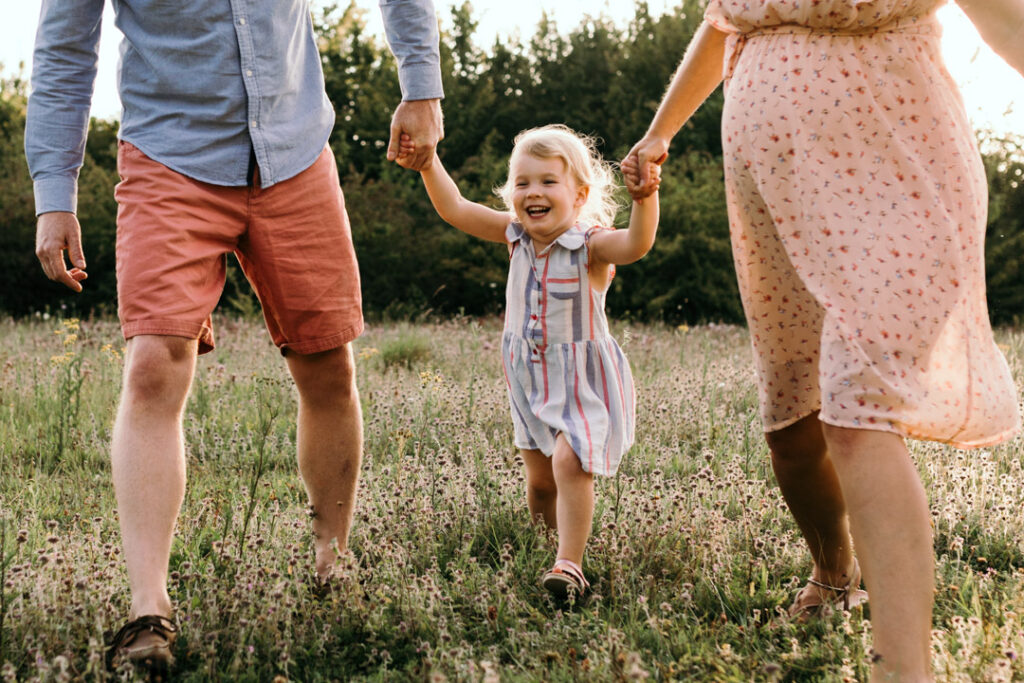 Mum and dad are holding their daughter hands. Little girl is laughing. Golden hour maternity photography in Hamsphire. Ewa Jones Photogarphy