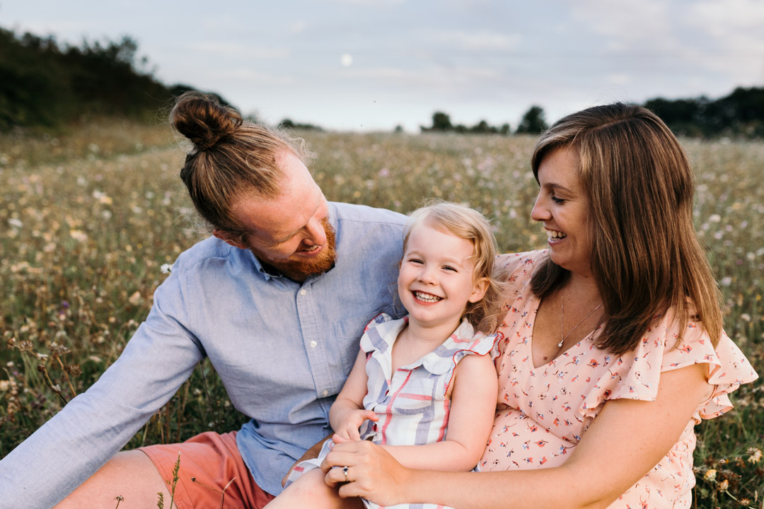 Mum, dad and little girl are sitting on the grass and laughing. Lovely family photo session during golden hour. Maternity photography in Hampshire. Ewa Jones Photography