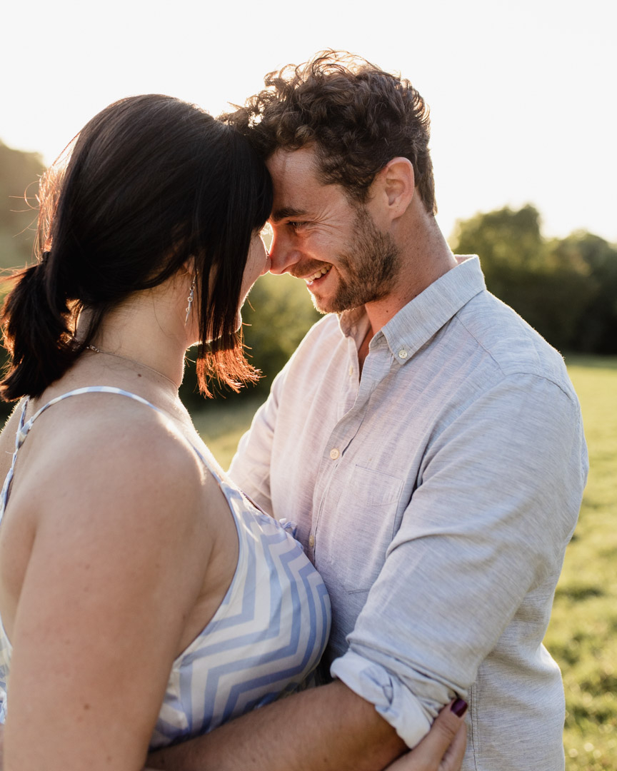 Dad is looking at his pregnant partner. Lovely golden hour setting. Maternity photographer in Basingstoke. Ewa Jones Photography