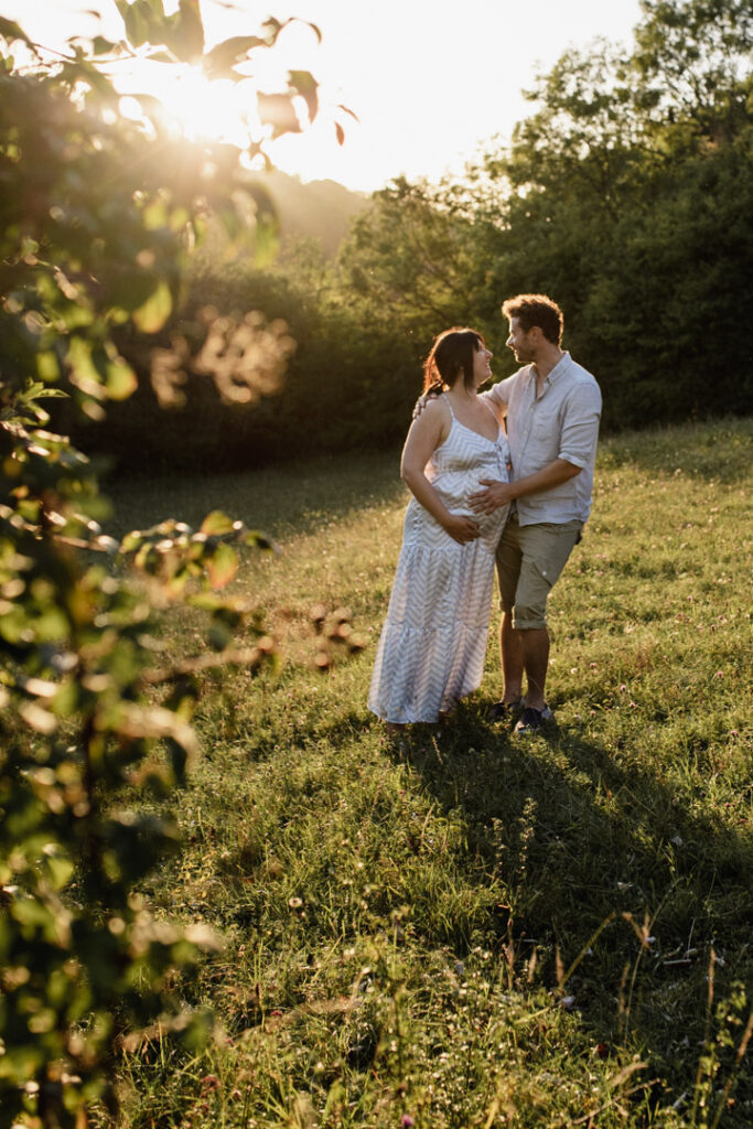 Expecting mum and partner are looking at each other and standing in the field. Lovely golden sun maternity photo session. Ewa Jones Photography