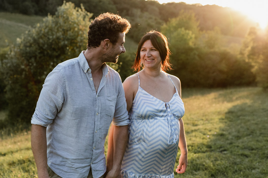 Pregnant mum is looking at her partner. They are both holding hands and looking at each other. Lovely golden hour maternity photo session. Ewa Jones Photography