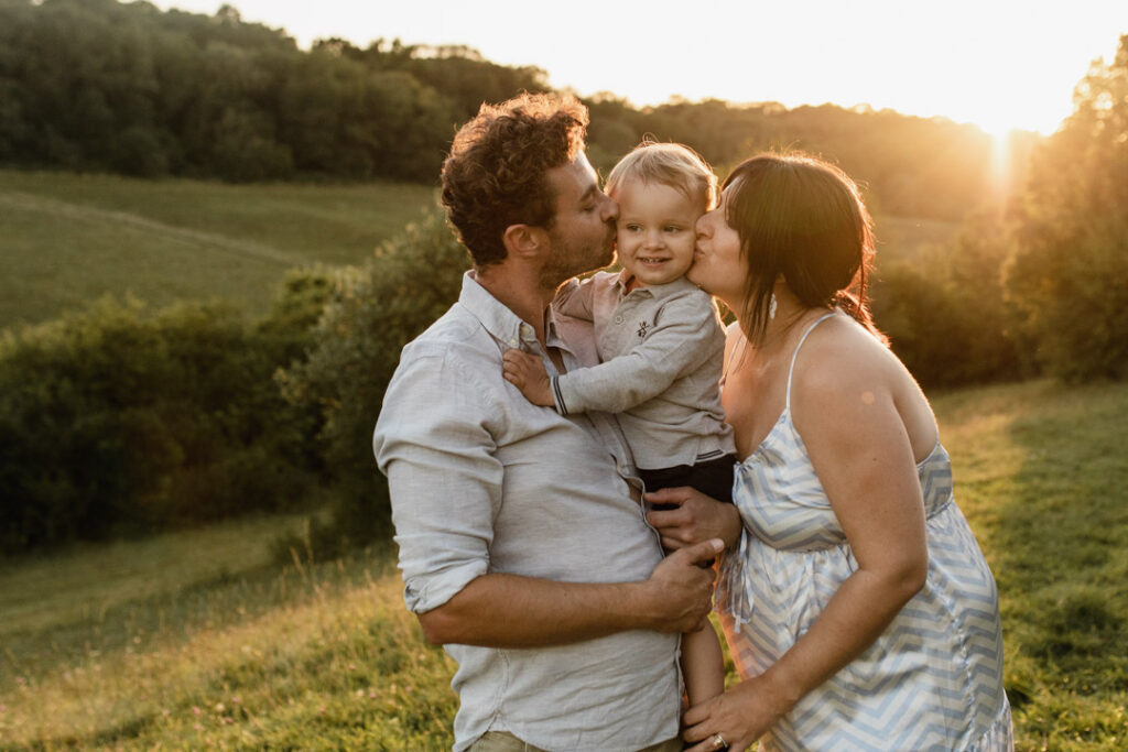 Expecting mum is kissing her toddler boy and dad is kissing his boy. Mum is wearing lovely maternity dress and dad and boy are wearing light blue shirts. What to wear for a maternity photo session. Ewa Jones Photography