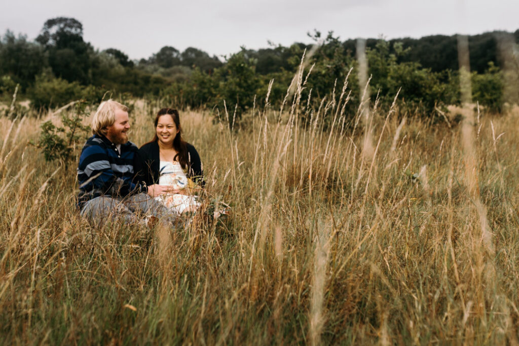 Expecting mum and dad are sitting on the grass and laughing. Lovely candid maternity photography in Hampshire. Ewa Jones Photography