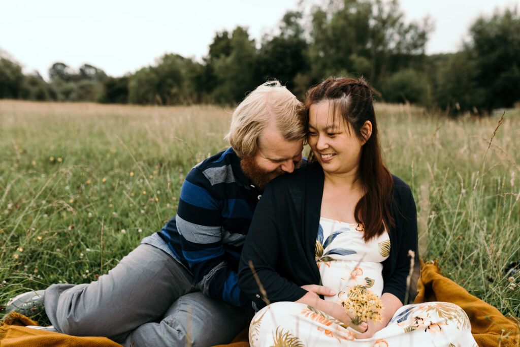 Pregnant mum is sitting on the blanket and her husband is hissing her shoulder. Expecting mum is holding lovely yellow flowers. Ewa Jones Photography