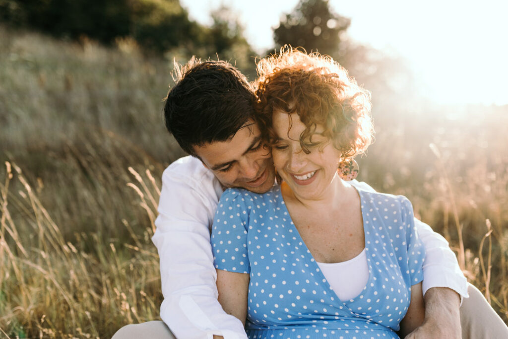Husband and wife are sitting on the grass and smiling. Golden hour maternity photo session in Hampshire. Ewa Jones Photography