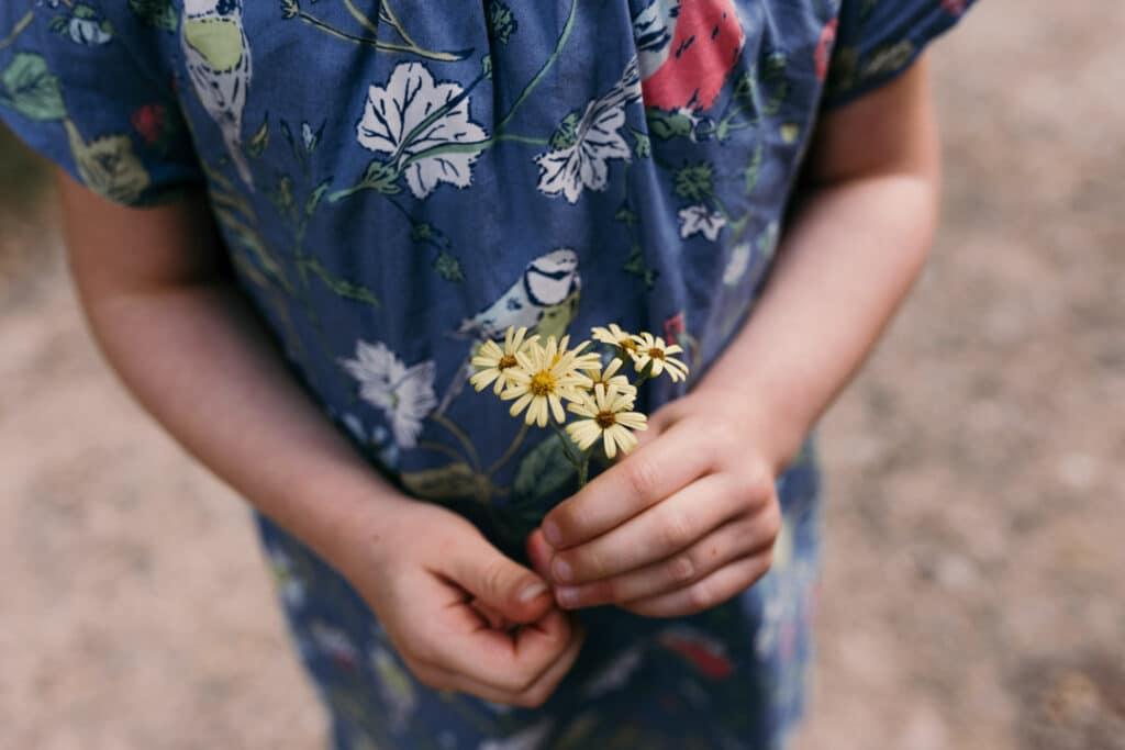 Girl dressed in blue dress is holding yellow flowers. lovely family lifestyle photography in Basingstoke. Ewa Jones Photography