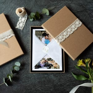 Photography gift vouchers. Gift voucher is in the middle lovely wrapped in tissue paper and inside brown box. on the side there are flowers and ribbons. Photography gift vouchers. Ewa Jones Photography