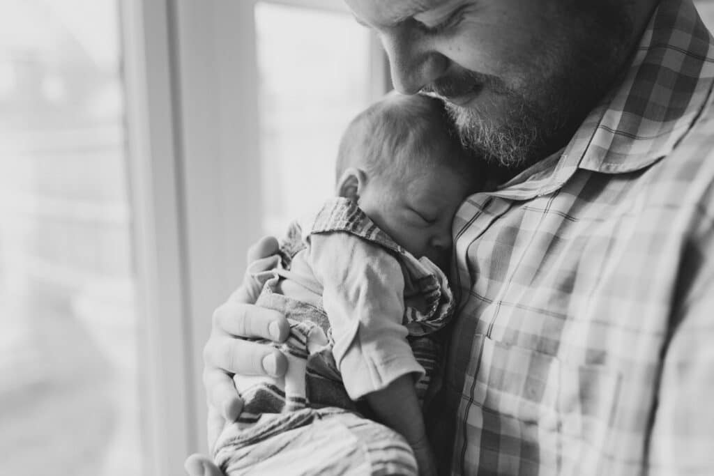 Dad is holding his newborn baby boy close to his chest. Baby boy is sleeping. Newborn photographer in Hampshire. Ewa Jones Photography