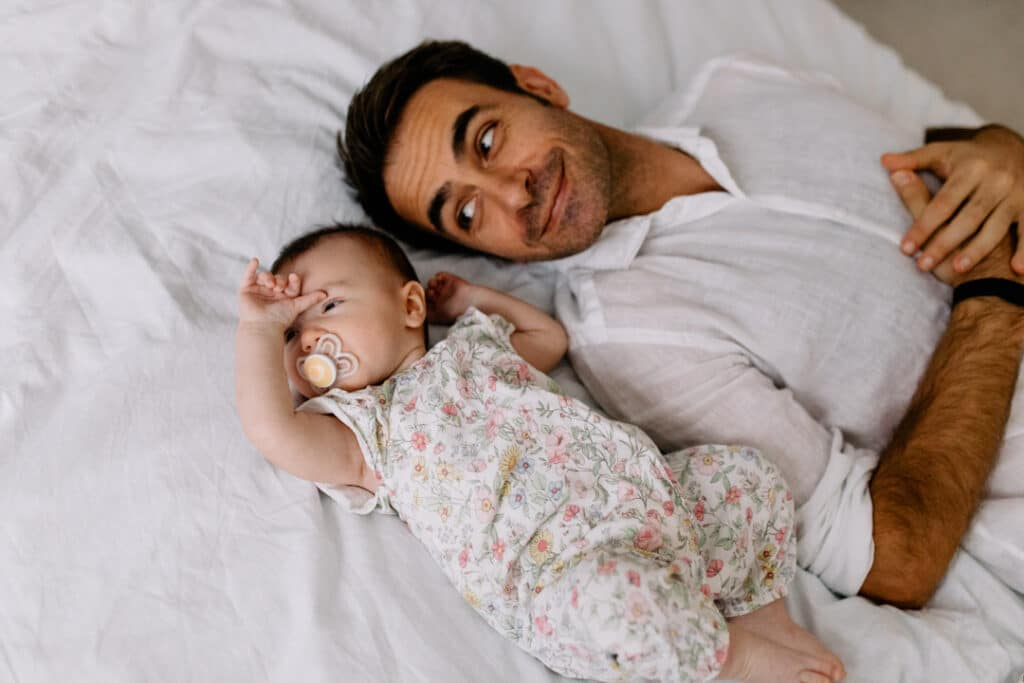Dad is laying on bed and looking at his baby daughter. His daughter is laying next to her dad and wearing lovely flowery baby grow. What to wear for your newborn baby photo shoot. Newborn baby photographer in Hampshire. Ewa Jones Photography