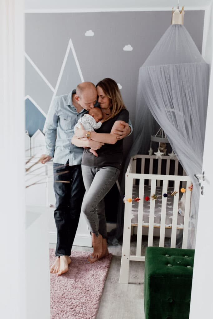Mum and dad are standing in little baby girl room. Mum is holding newborn baby girl and dad is kissing his baby. They are all looking lovely and happy. Newborn photography in Basingstoke, Hampshire. Ewa Jones Photography