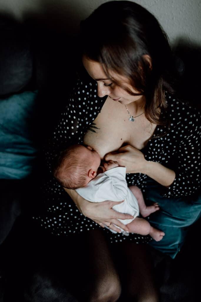 Mum is breastfeeding her newborn baby and sitting on the sofa. Mum is wearing black dress with white dots and baby is wearing a newborn baby grow. Newborn photographer in Hampshire. Ewa Jones Photography