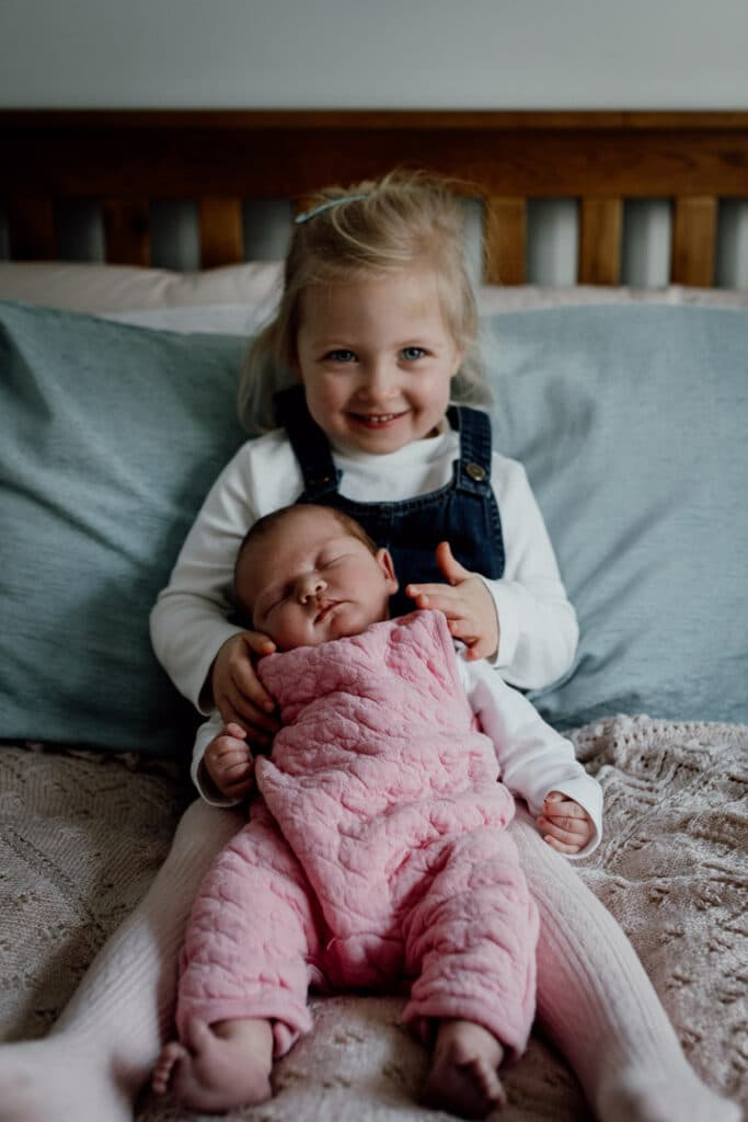 Older sister is sitting on the bed and holds her little newborn baby sister. Newborn baby is sleeping and wearing pink dungarees and older sister is wearing blue dress. Newborn photography in Basingstoke, Hampshire. Ewa Jones Photography