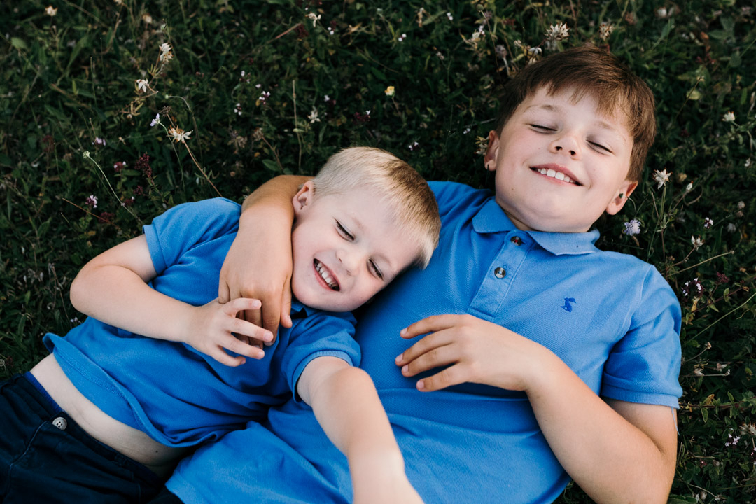 two cousins are laying on the grass and have eyes closed. They are both smiling. Both boys are wearing blue tops and shorts. family photographer in Hampshire. Ewa Jones Photography