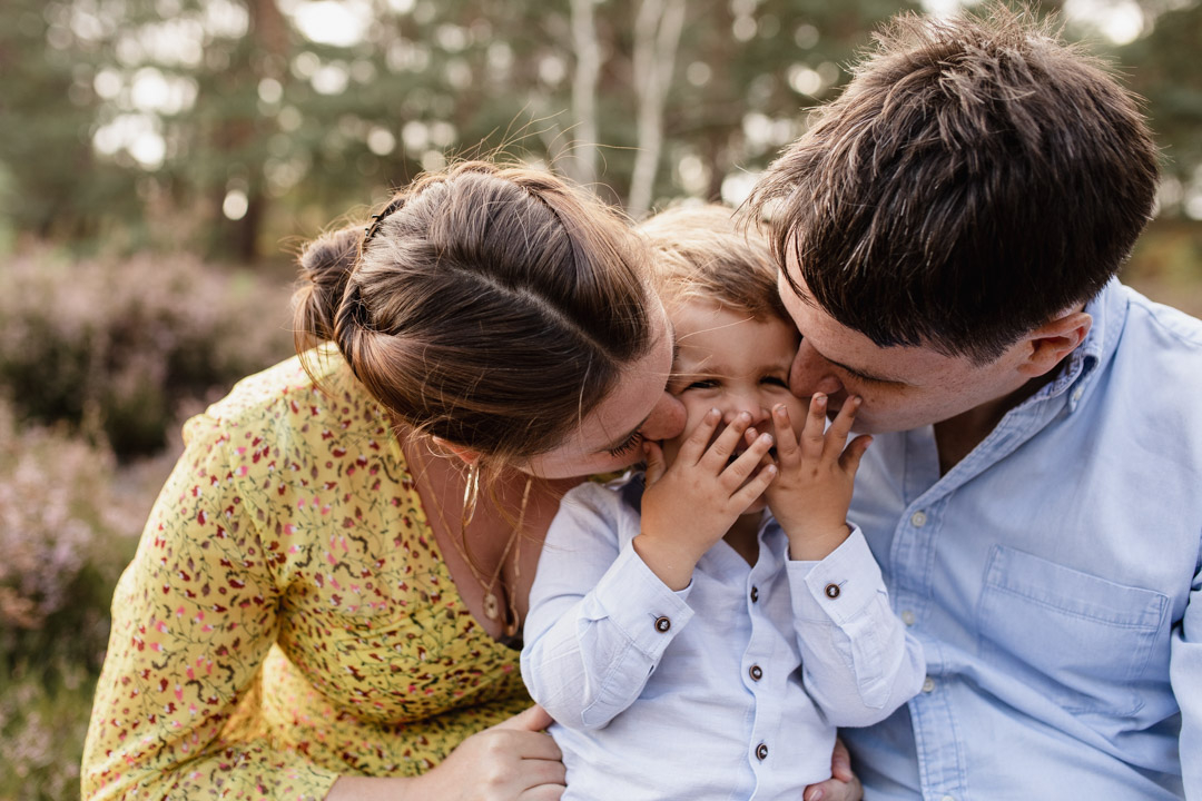 Mum and dad are sitting on the ground and kissing their little boy on the cheeks. Mum is wearing lovely yellow dress and dad and son are wearing blue shirts. Lovely candid family moment. Documenting family photography. Family photographer in Hampshire. Ewa Jones Photography