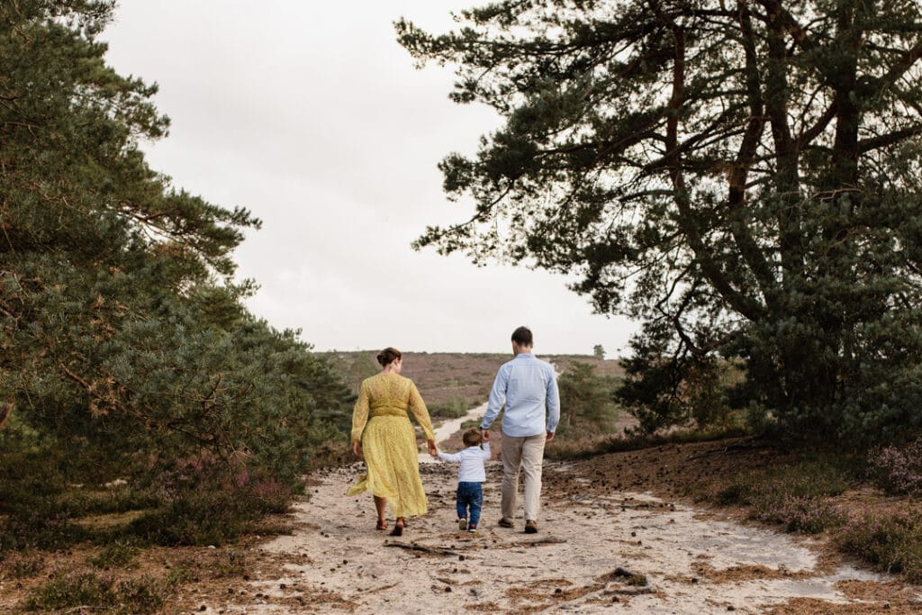 Mum, dad and their son are walking away in the lovely common in Fleet. Lovely golden hour family photo shoot in Hampshire. Family photography in Hampshire. Ewa Jones Photography