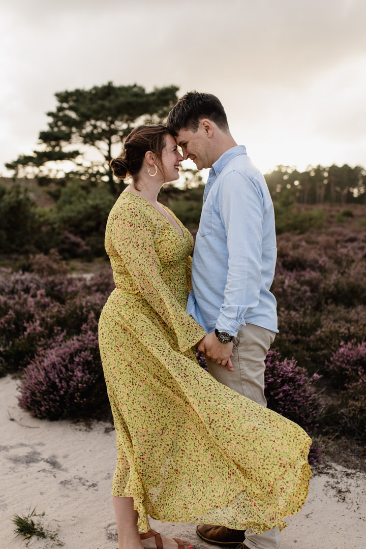 Mum and dad are holding hands together and are touching foreheads. Mum is wearing lovely yellow dress and dad is wearing blue shirt and light cream chinos. They are standing in the lovely common. Purple heather is on the ground. Family photographer in Hampshire. Ewa Jones Photography