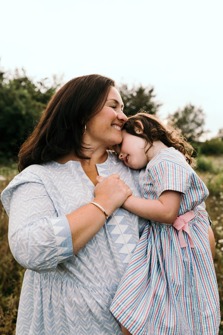 Mum is holding her daughter and is holding her hand close to her chest. Mum is smiling and daughter head is resting on mums shoulders. Lovely mum and daughter moment. Family photography in Basingstoke, Hampshire. Ewa Jones Photography