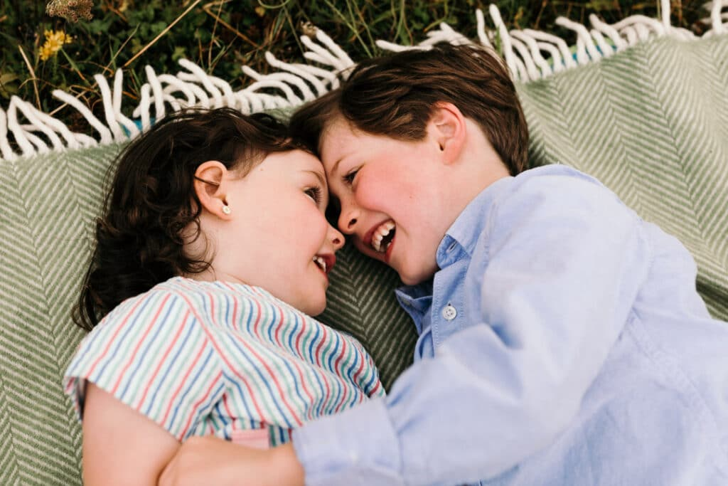 Sister and brother are laying on the blanket and looking at each other and giggling. their foreheads are touching. Family lifestyle photography in Hampshire. Ewa Jones Photography