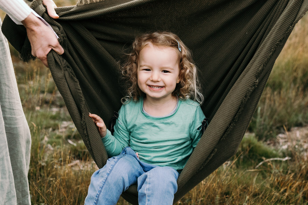 Little girl is sitting inside the blanket and smiling at the camera. Family photographer in Hampshire. Ewa Jones Photography