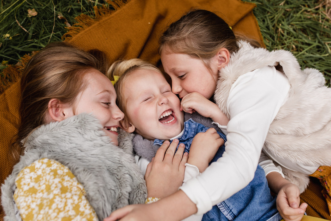 Three sisters are laying on the blanket and hugging each other. They are all wearing lovely autumnal clothing. Golden hour autumn photo session in Basingstoke, Hampshire. Ewa Jones Photography