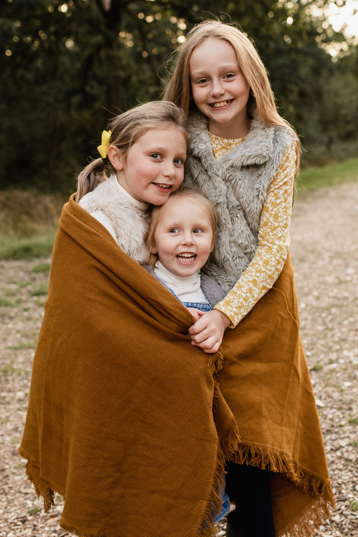 Three sisters are cuddling up inside the blanket. They are all smiling. Family photo session in Basingstoke, Hampshire. Ewa Jones Photography