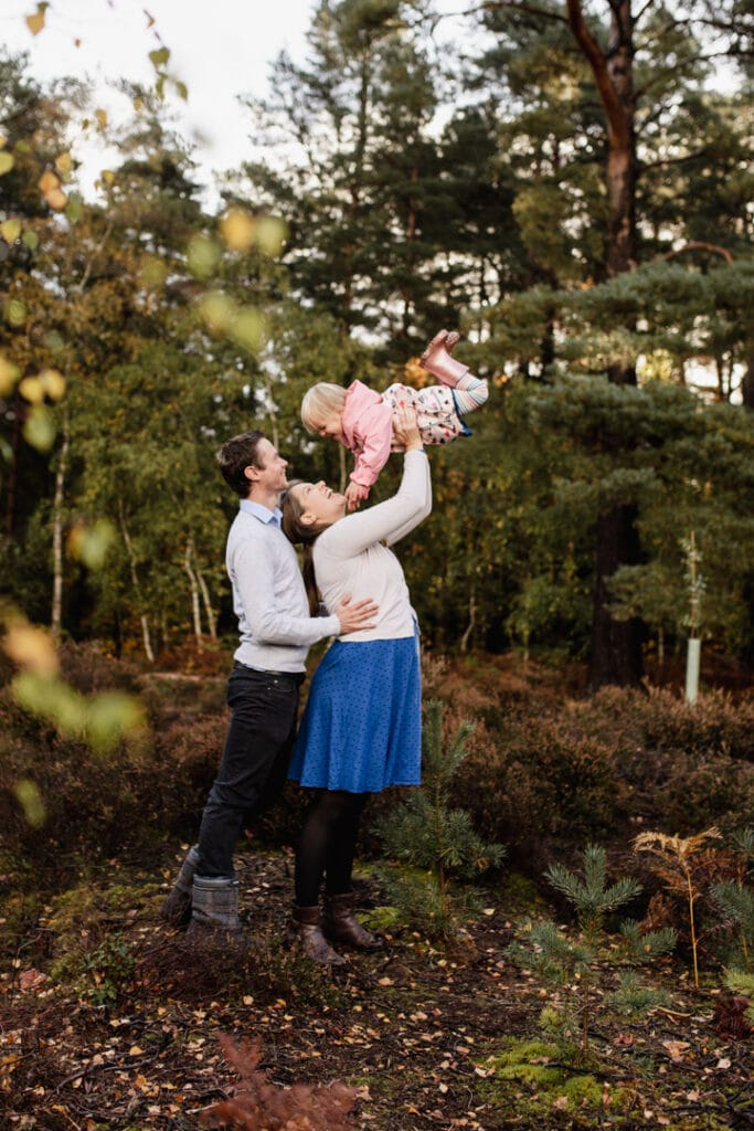 Mum is lifting into the air her little girl and dad is standing behind. Family autumnal photo session in Surrey. Family photographer. Ewa Jones Photography