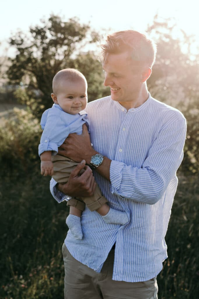 Dad is holding his six month old baby boy and looking at him. Little boy is smiling. Lovely sun is shining behind dad. Family photographer in Hampshire. Ewa Jones Photography