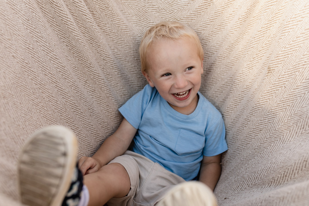 Little boy is inside the blanket and smiling. He is wearing blue top and cream shorts. Candid family photography in Hook, Hampshire. Ewa Jones Photography