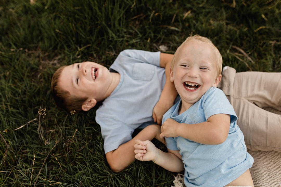 One brother is laying on the grass laughing and another brother is laying on his sibling. Younger brother is laughing too. Family photographer in Hampshire. Ewa Jones Photography