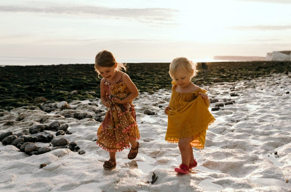 Family holiday in Hastings. Two little girls are walking on the beach at Seven sisters. Ewa Jones Photography