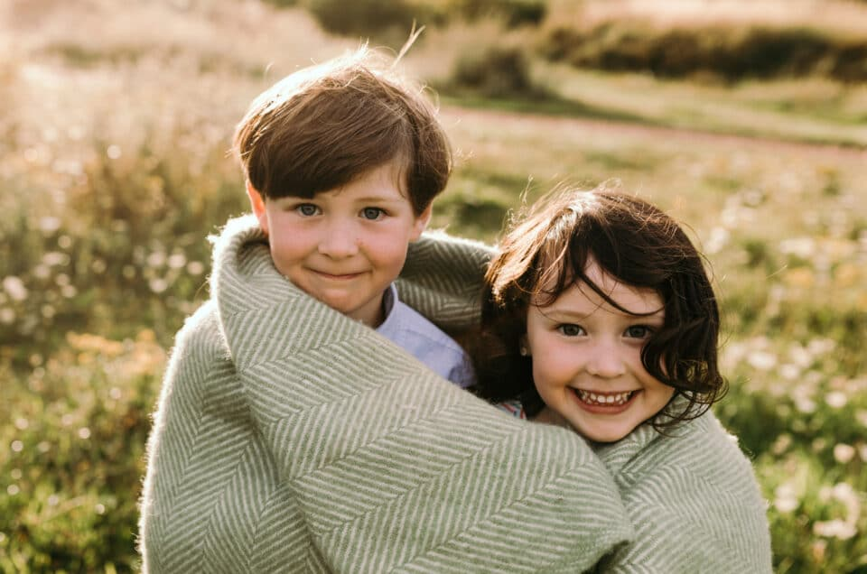 Brother and sister are wrapped around the blanket and looking at the camera. Lovely summer evening. Family photographer in Hampshire. Ewa Jones Photography