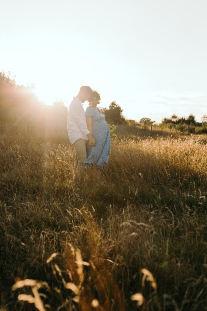 Expecting parents are holding hands and touching heads. Sun is behind them. Lovely maternity photo session during golden hour. Maternity photographer in Basingstoke, Hampshire. Ewa Jones Photography