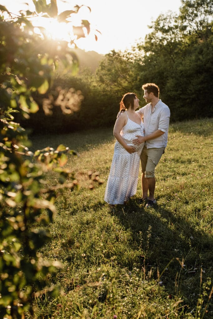 Mum and dad are standing next to each other and looking at each other and smiling. Lovely maternity photo session during golden hour. Maternity photographer in Hampshire. Ewa Jones Photography