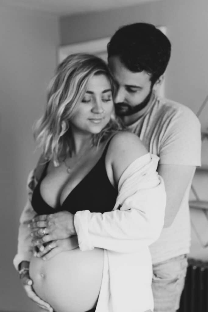 Pregnant mum is standing in baby nursery and her husband is hugging her and baby bump. Lovely in home maternity photography in hampshire. Ewa Jones Photography