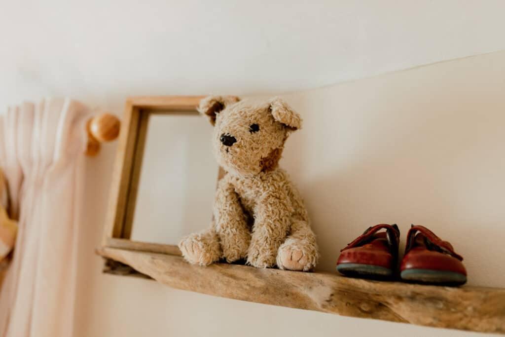 Baby nursery, rustic look. teddy bear and baby shoes on the shelf. Ewa Jones Photography