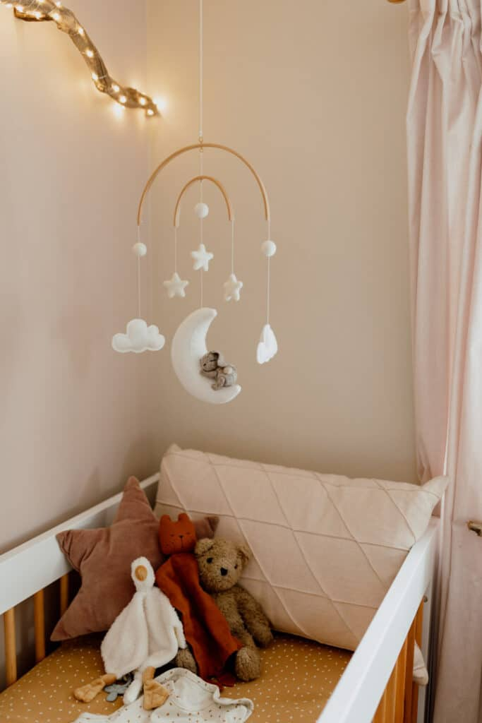 Close up of baby cot with lovely toys and cot mobile. In home maternity photo session in Hampshire. Ewa Jones Photography