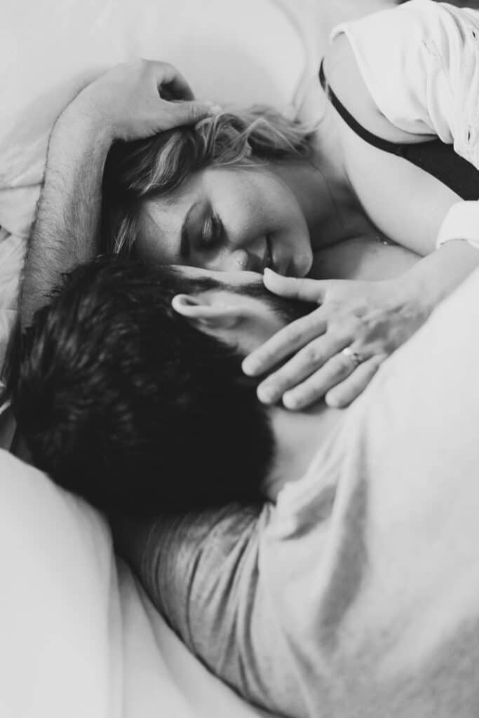 Black and white photography of a couple laying on bed and looking at each other. Intimate maternity photo session in Hampshire. Ewa Jones Photography
