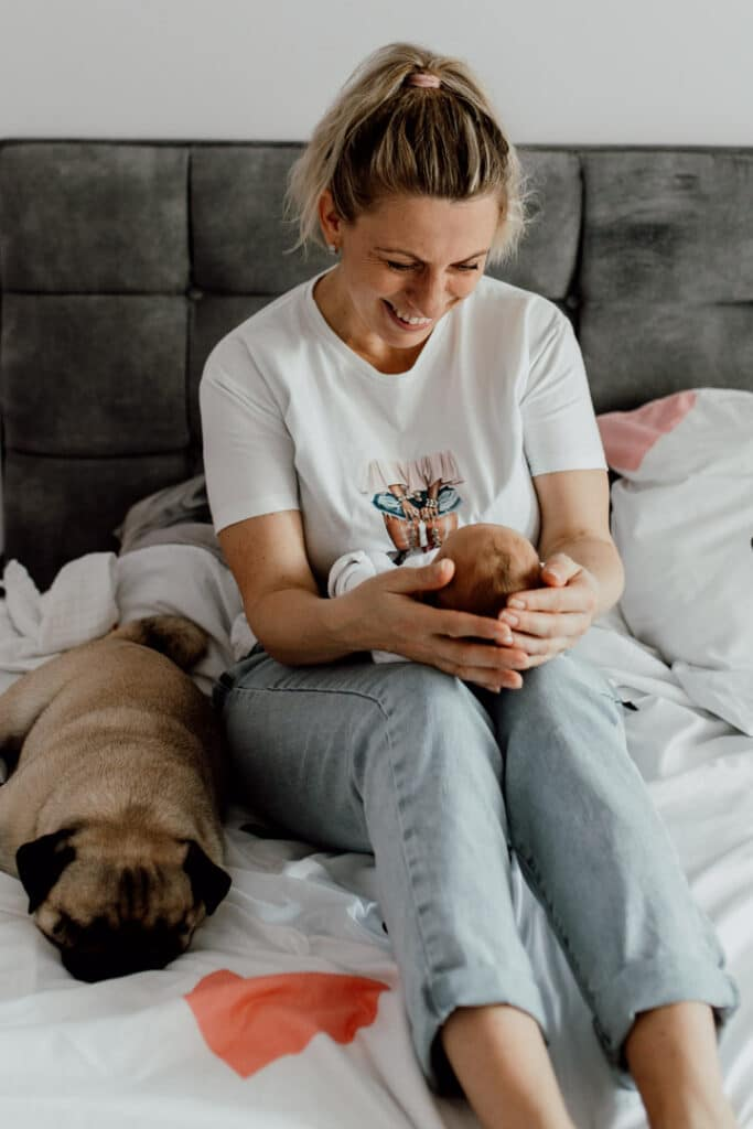 Mum is sitting on the bed and looking down at her baby girl. she is smiling at her girl. Next to mum is laying their dog. Newborn lifestyle photography in Hampshire. Ewa Jones Photography