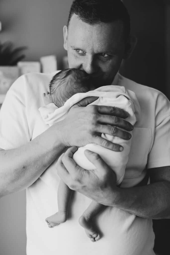Black and white picture of dad holding a newborn baby. Newborn baby is sleeping in his arms. Newborn photography in Hampshire. Ewa Jones Photography
