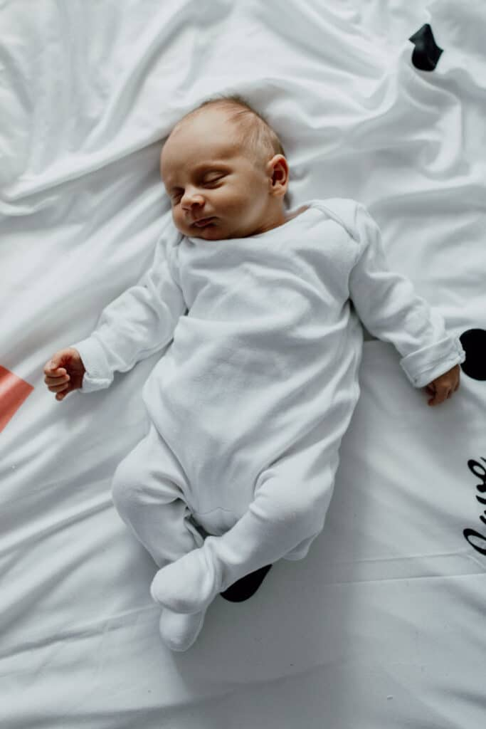 Newborn baby is wearing white baby grow and she is laying on the bed sleeping. in-home lifestyle newborn baby photo session in Hampshire. Ewa Jones Photography