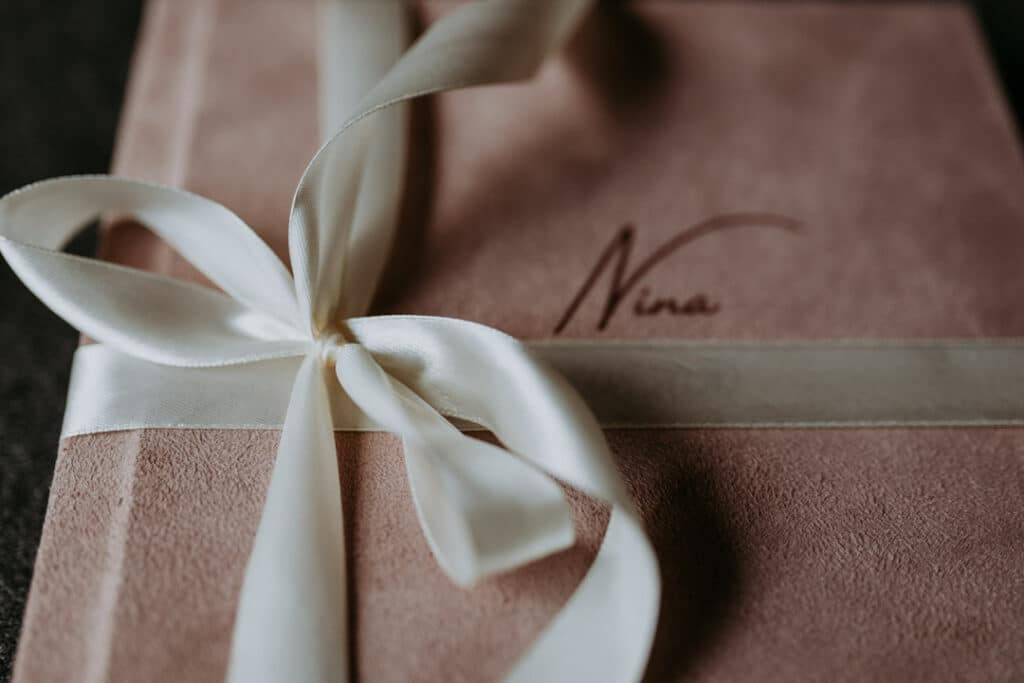 Close up detail of a newborn photo album. Pink cover with white ribbon. Newborn photography in Basingstoke. Ewa Jones Photography