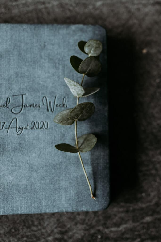 Family photo album in blue colour on dark background. Family photographer in Basingstoke. Ewa Jones Photography