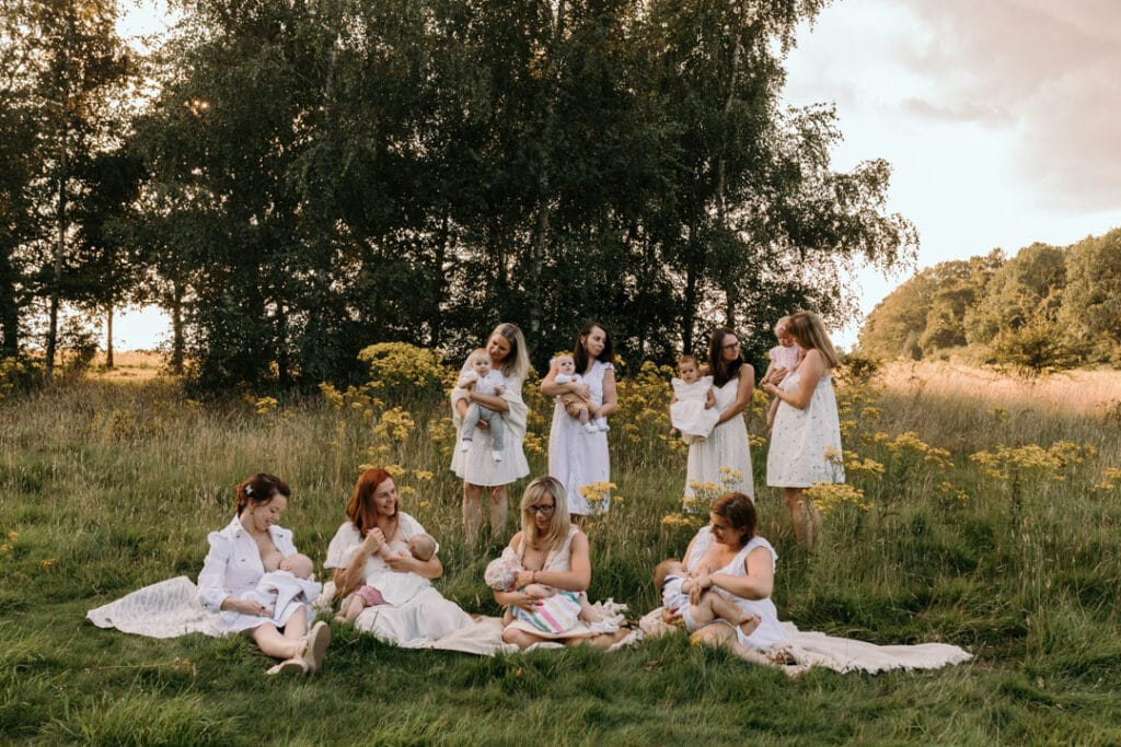 mums are sitting on the blanket and breastfeeding their babies. There is a gorgeous field full of wild flowers and the sun is shining through the trees. Group breastfeeding photo session Basingstoke, Hampshire. Ewa Jones Photography