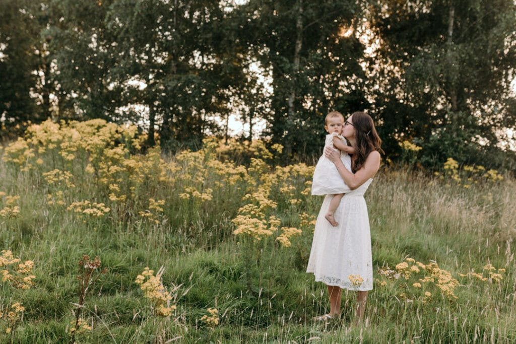 Mum is standing on the field of wild flowers and holding her girl. Mum is kissing her little girl on the cheek. Lovely family photography in Hampshire. Ewa Jones Photography