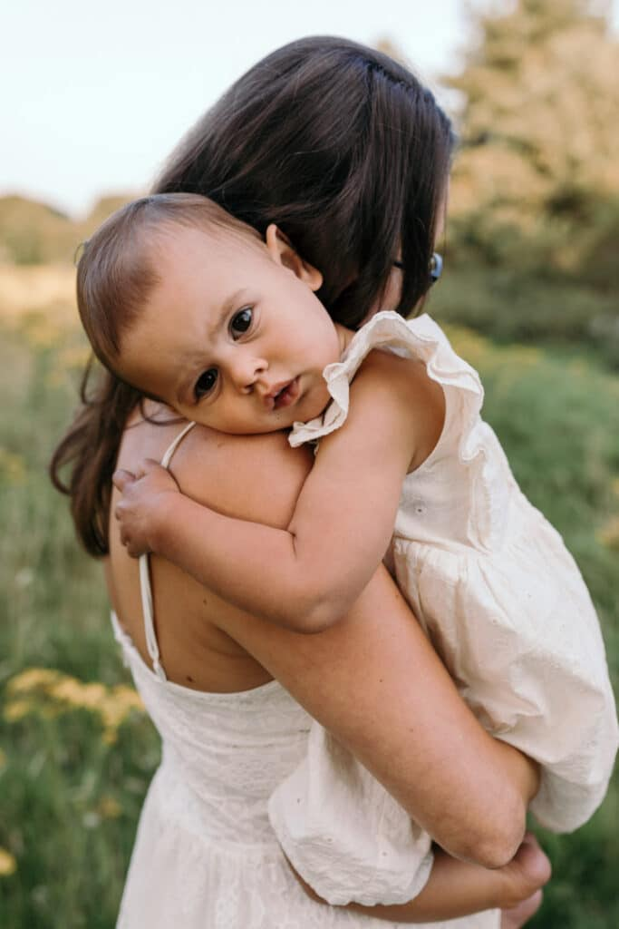 Little girl is laying gently on mummys arms. She is looking at the camera. Little girl is wearing lovely white dress. Family photographer in Basingstoke, Ewa Jones Photography