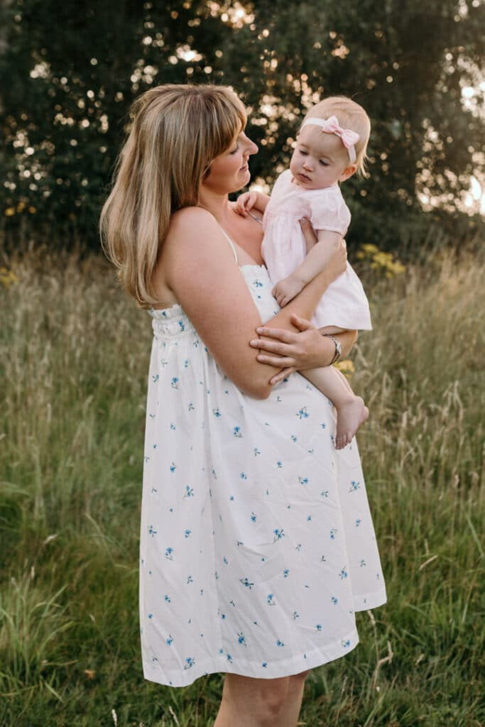 Mum is holding her little girl in her arms a looking at her. Sun is shining and mum is wearing white dress with blue flowers and girl is wearing lovely pink dress. Family photographer in Basingstoke, Hampshire. Ewa Jones Photography