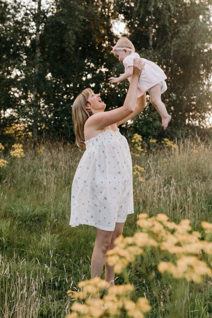 Mum is lifting her little girl up and smiling at her. Photo session during golden hour. Family photography in Basingstoke, Hampshire. Ewa Jones Photography