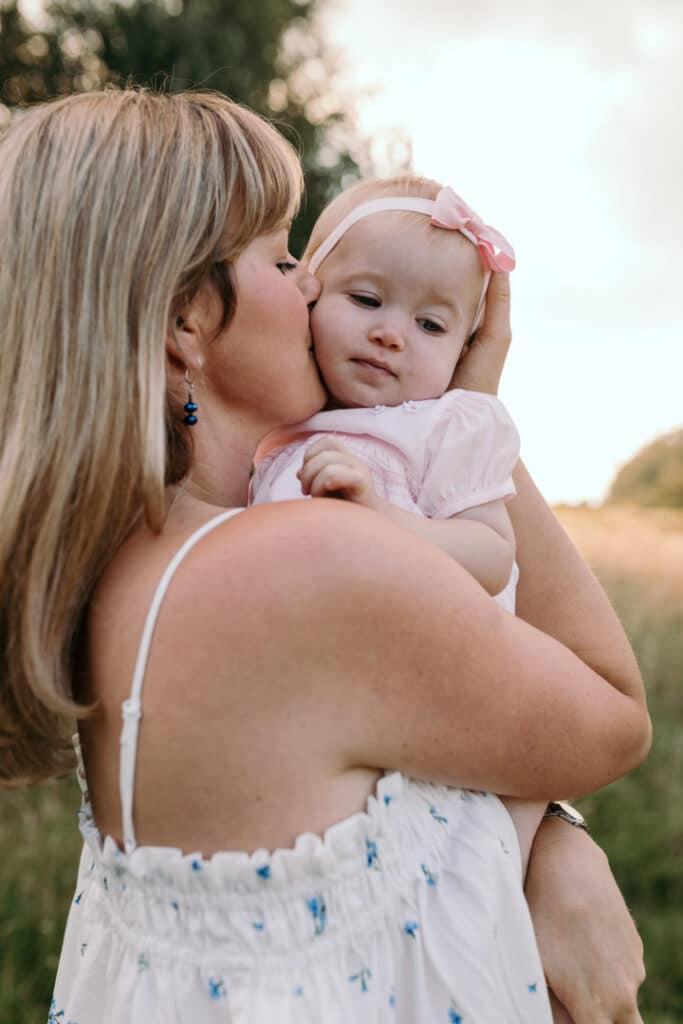 Mum is kissing her little baby girl on her cheek. Sunset family photography. Family photographer in Basingstoke, Hampshire. Ewa Jones Photography